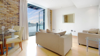 Living room and balcony with river view at a Tea Trade Wharf show apartment, ©Galliard Homes.