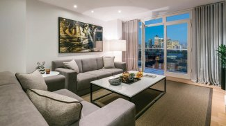 Living area in a Galliard Homes apartment with a view of Canary Wharf, ©Galliard Homes.